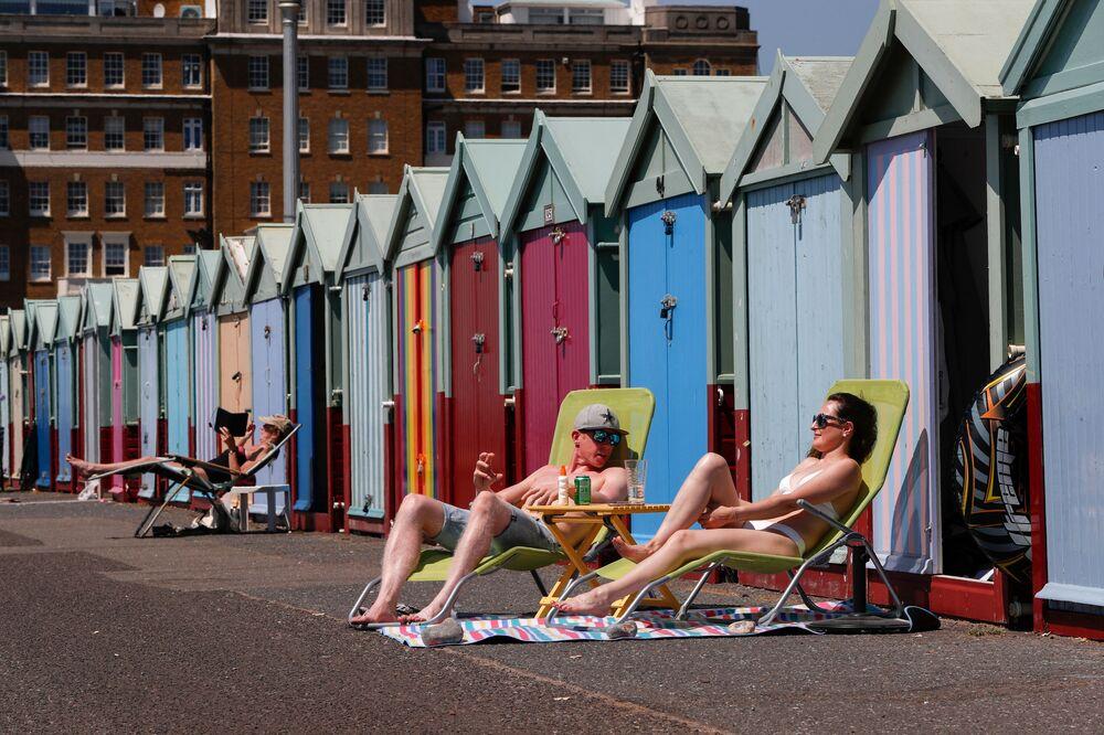 Lidé se opalují před plážovými chatami v britském Brightonu