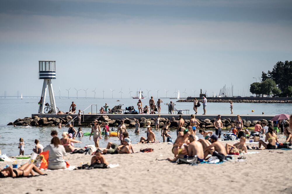 Lidé si užívají horkého počasí na pláži Bellevue severně od Kodaně, Dánsko