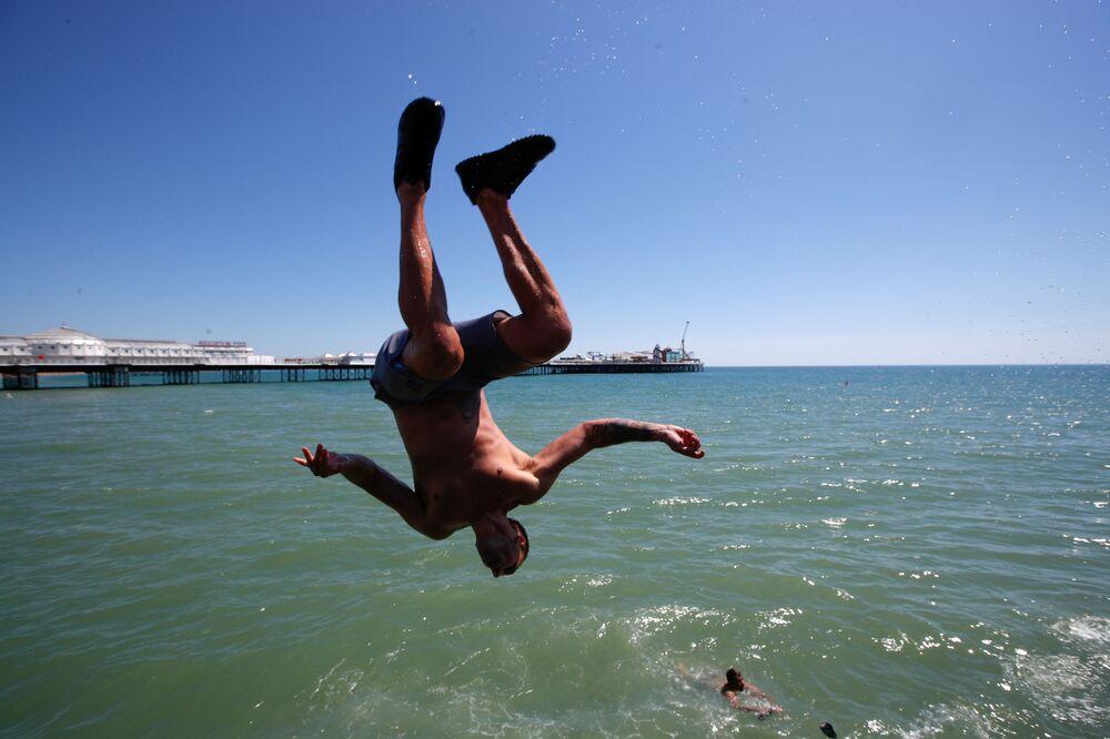 Muž skáče do vody na pláži v Brightonu, Velká Británie