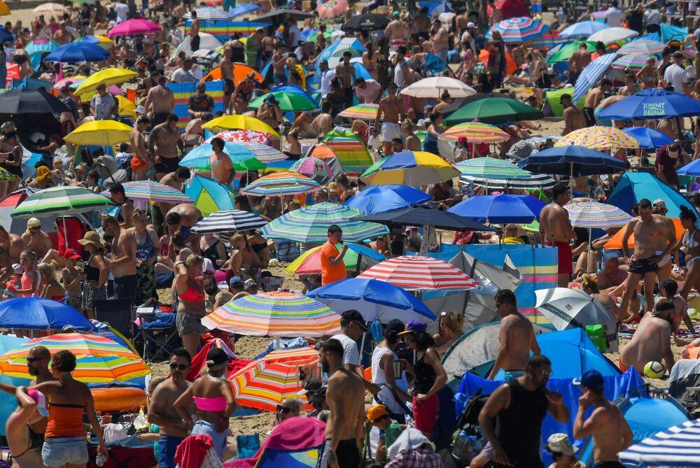 Lidé si užívají horkého počasí na pláži v Bournemouthu, Velká Británie