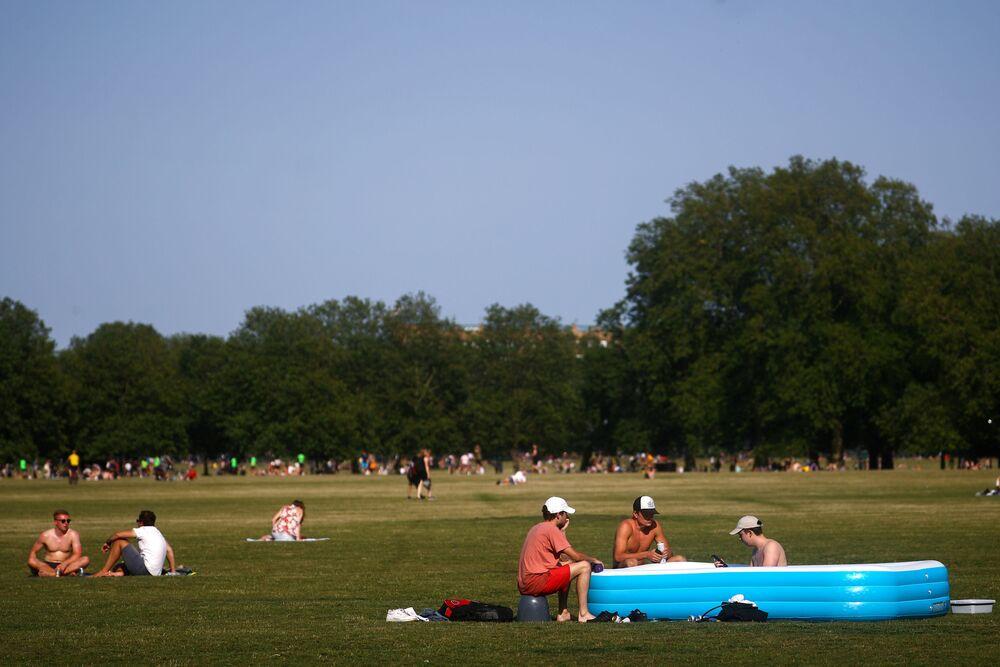 Lidé odpočívají v nafukovacím bazénu v Londýně, Velká Británie