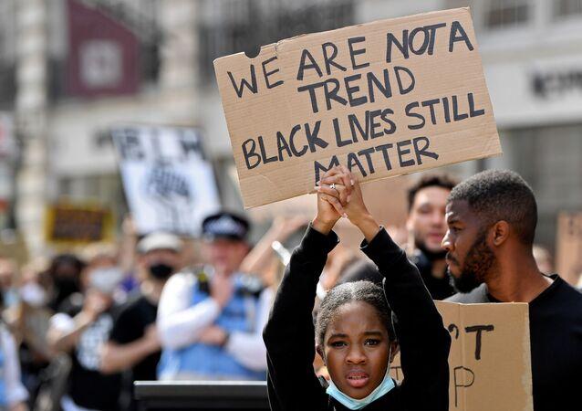Demonstranti drží ceduli během protestů Black Lives Matter v Londýně