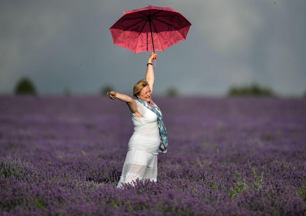 Žena s deštníkem na levandulovém poli na Krymu