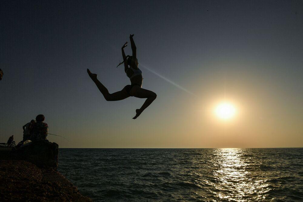 Dívka skáče z mola na krymské pláži