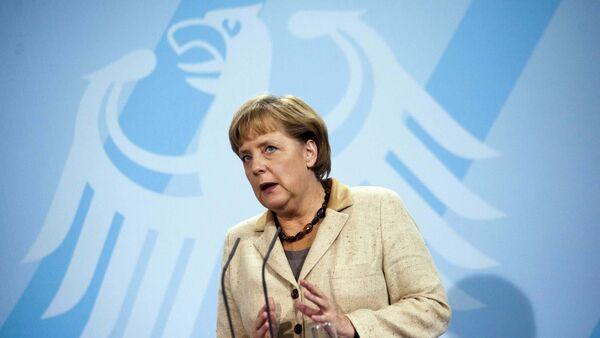 German Chancellor Angela Merkel  in front of Germany's heraldic eagle - Sputnik Česká republika