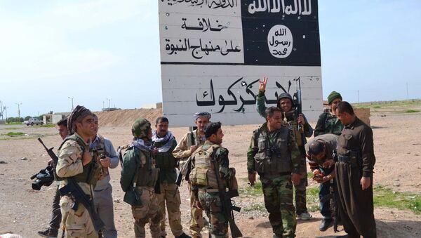 Kurdští povstalci na pozadí symbolu IS - Sputnik Česká republika