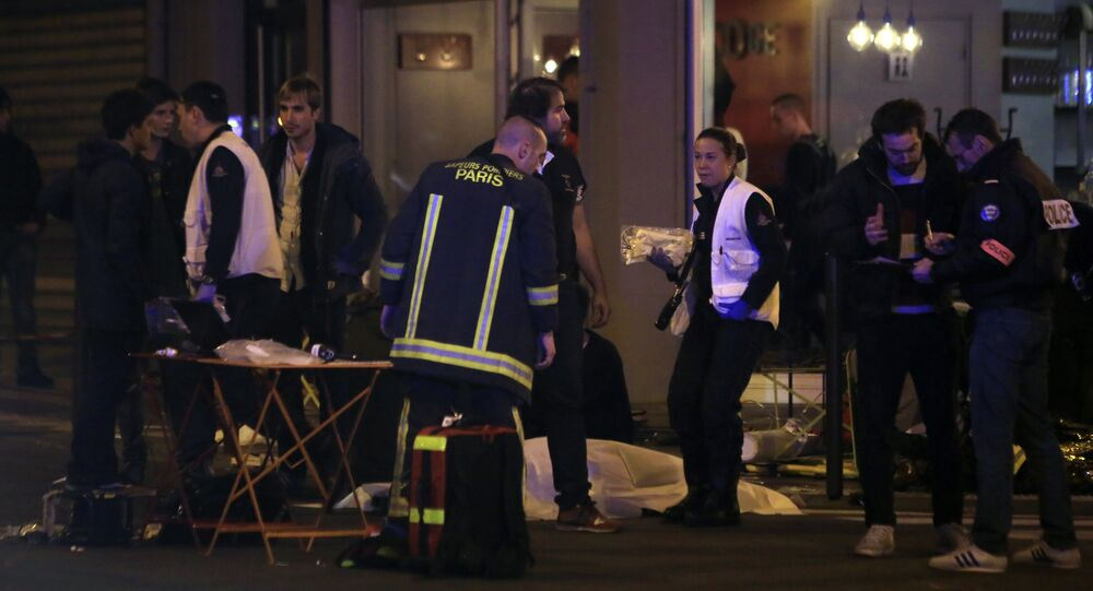 Rescue workers and medics work by victims in a Paris restaurant, Friday, Nov. 13, 2015.