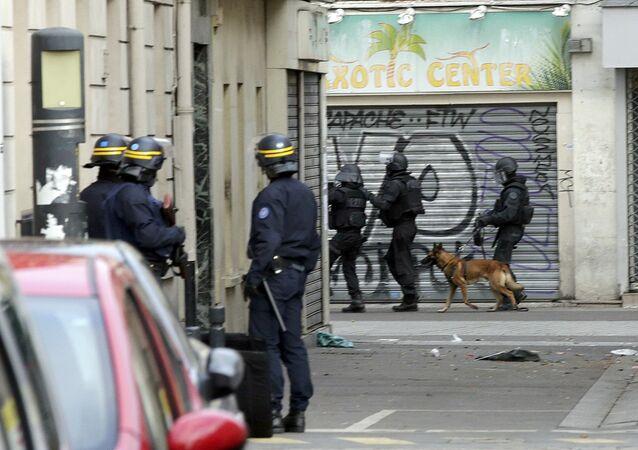 Příslušníci francouzských zásahových jednotek a služební pes