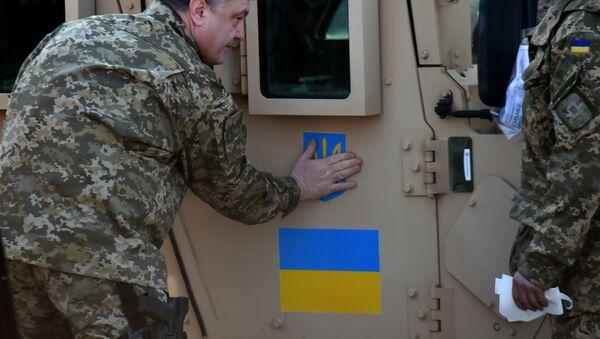 Ukrajinský prezident Petro Porošenko nalepuje ukrajinskou vlajku na Humvee - Sputnik Česká republika