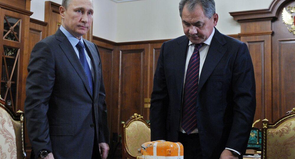 Russian Defense Minister Sergei Shoigu shows President Vladimir Putin a flight recorder of a Russian warplane shot down by a Turkish jet on Nov. 24.