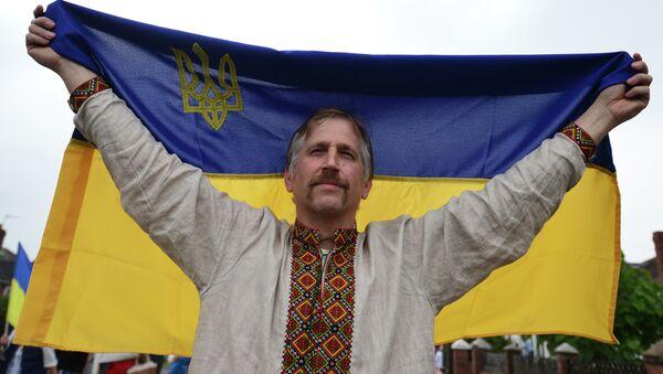 Muž drží ukrajinskou vlajku - Sputnik Česká republika