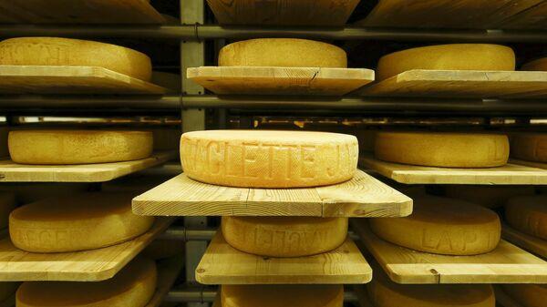 Sýr Raclette, výrobek společnosti Seiler Käserei AG, zraje na  policích v bývalém skladu střeliva Giswil. - Sputnik Česká republika