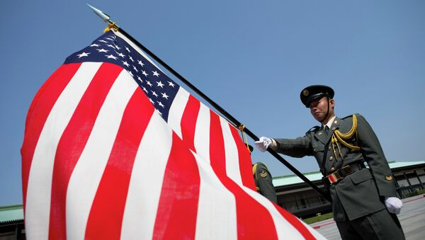 Japanese soldier holds and American Flag as President Barack Obama participates in a welcome ceremony with Japanese Emperor Akihito's wife Empress Michiko at the Imperial Palace in Tokyo - Sputnik Česká republika