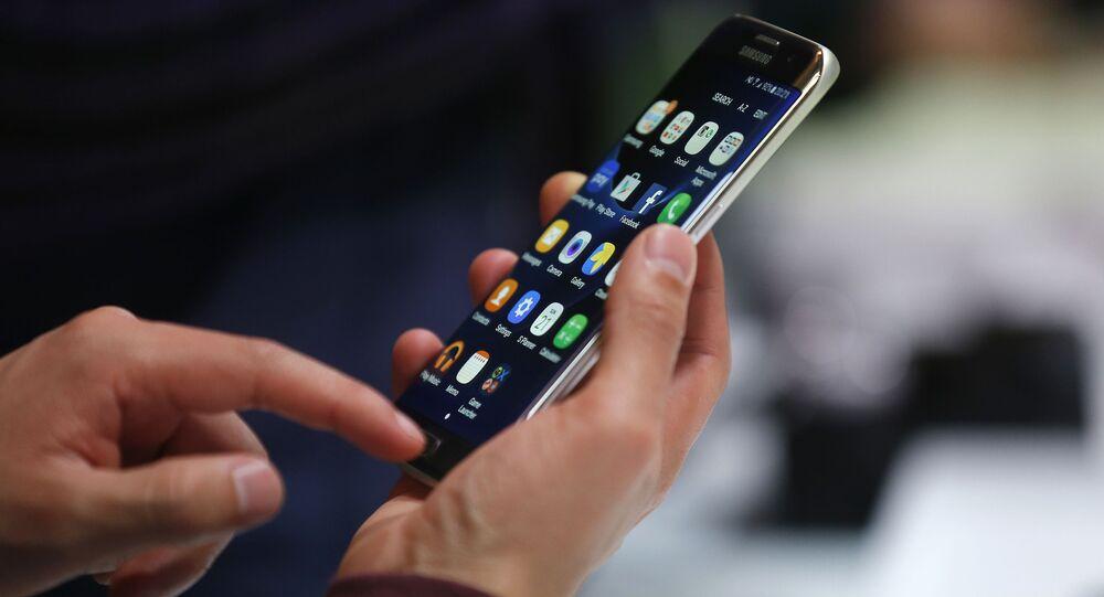 Muž drží v rukou chytrý telefon Galaxy S7 Edge