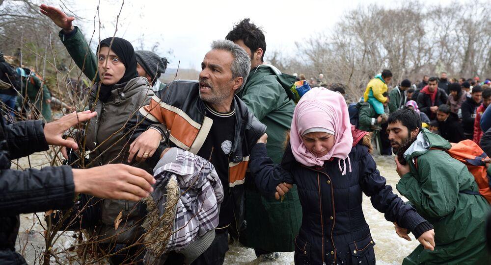 Uprchlíci a migranti překonávají řeku cestou do Makedonie z improvizovaného tábora na řecko-makedonské hranici