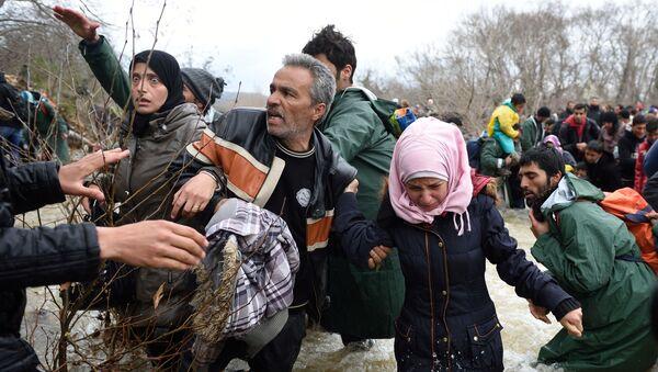 Uprchlíci a migranti překonávají řeku cestou do Makedonie z improvizovaného tábora na řecko-makedonské hranici - Sputnik Česká republika