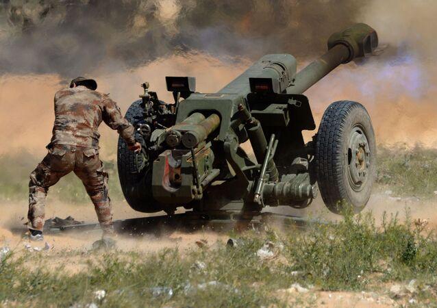 Voják syrské armády střílí z houfnice D-30 po pozicích bojovníků v okolí Palmýry v Sýrii