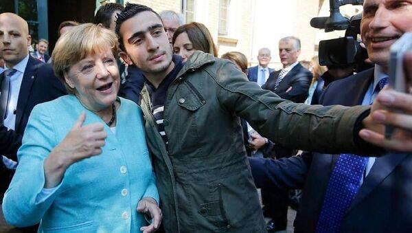 Anas Modamani a Angela Merkelová - Sputnik Česká republika