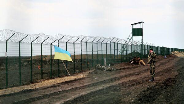 Ukrajinský pohraničník u plotu na hranici s Ruskem - Sputnik Česká republika