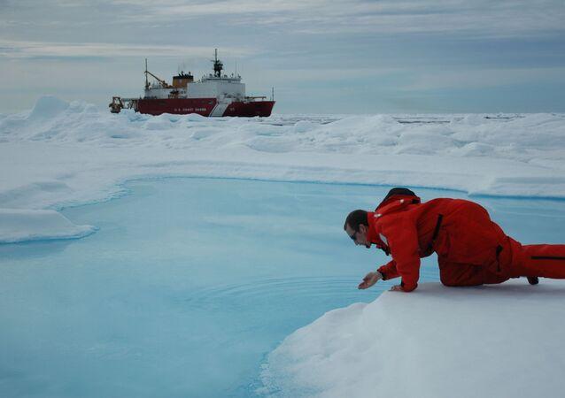 Vědec odebírá kontrolní vzorek vody v Arktidě