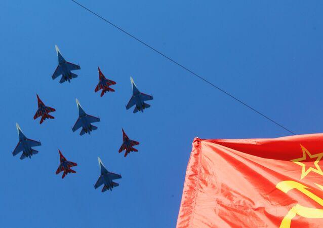 Pilotáží skupiny Ruští reci a Rorýsi v sestavě pěti letadel Su-27 a čtyř MiG-29