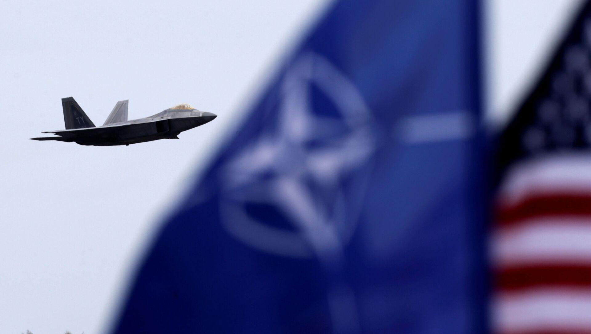 F-22 Raptor na pozadí vlajek USA a NATO - Sputnik Česká republika, 1920, 13.03.2021