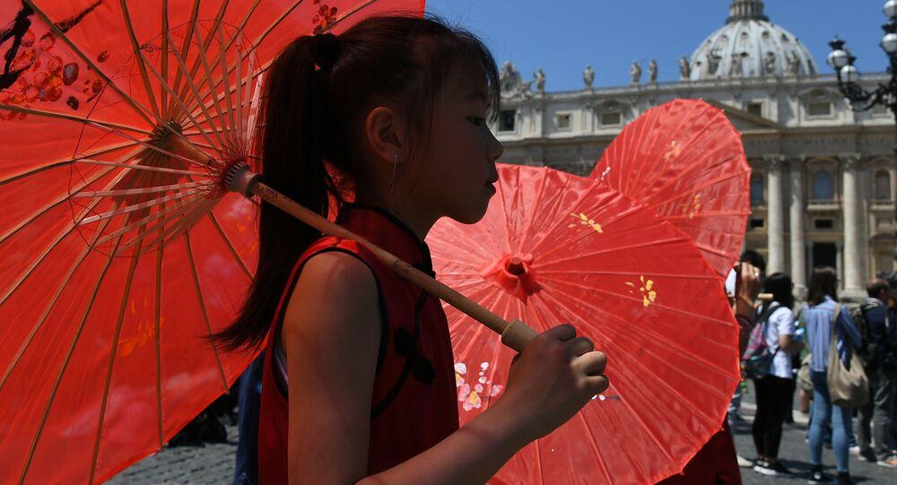 Dívka s červeným deštníkem prochází kolem papežovy rezidence ve Vatikánu
