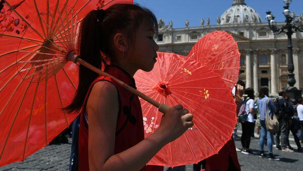 Dívka s červeným deštníkem prochází kolem papežovy rezidence ve Vatikánu - Sputnik Česká republika