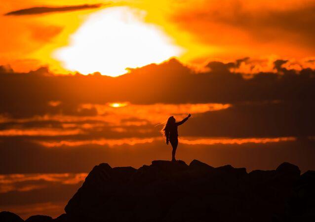 Dívka dělá selfie na Olympijském nábřeží v Adleru při západu slunce