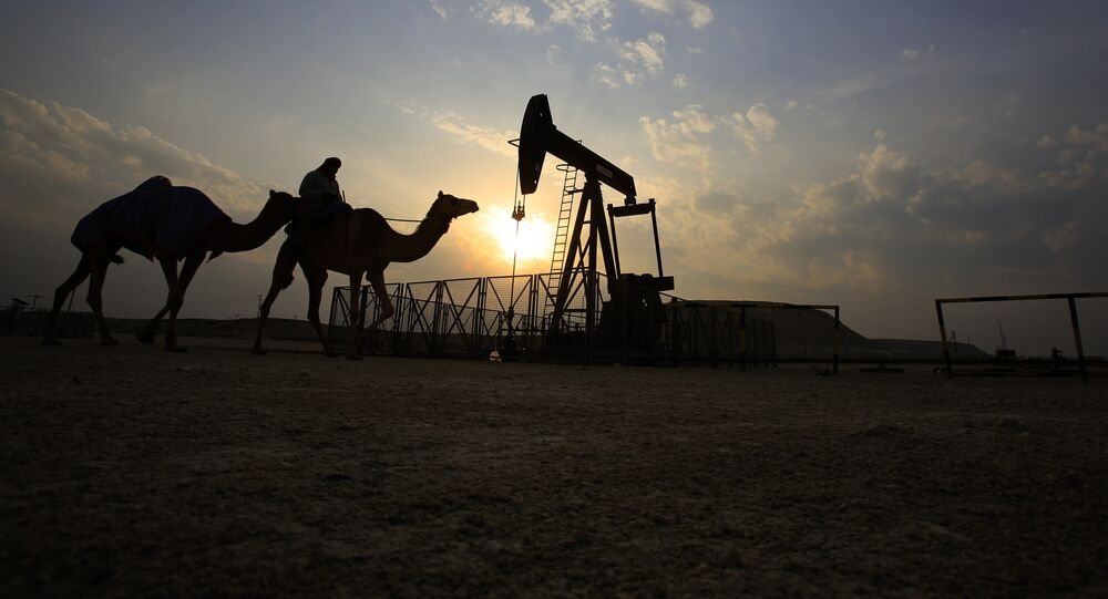 Muž projíždí v poušti na velbloudu okolo ropného vrtu v Sakhiru, Bahrain.