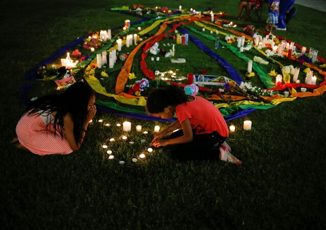 Ten-year-old twins Erica (L) and Olivia Hartley light candles after a vigil in memory of victims one day after a mass shooting at the Pulse gay night club in Orlando, Florida, U.S., June 13, 2016