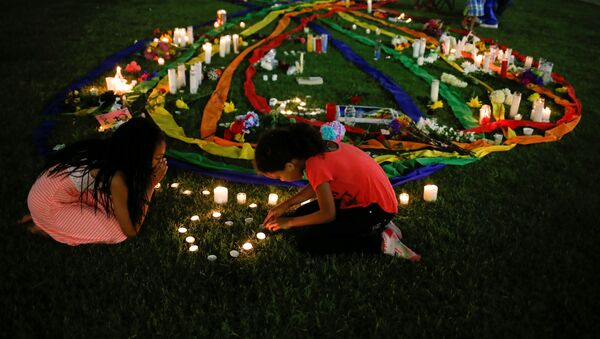 Ten-year-old twins Erica (L) and Olivia Hartley light candles after a vigil in memory of victims one day after a mass shooting at the Pulse gay night club in Orlando, Florida, U.S., June 13, 2016 - Sputnik Česká republika