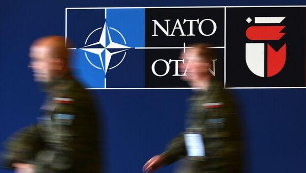 Muži u banneru summitu NATO ve Varšavě na Národním stadionu - Sputnik Česká republika