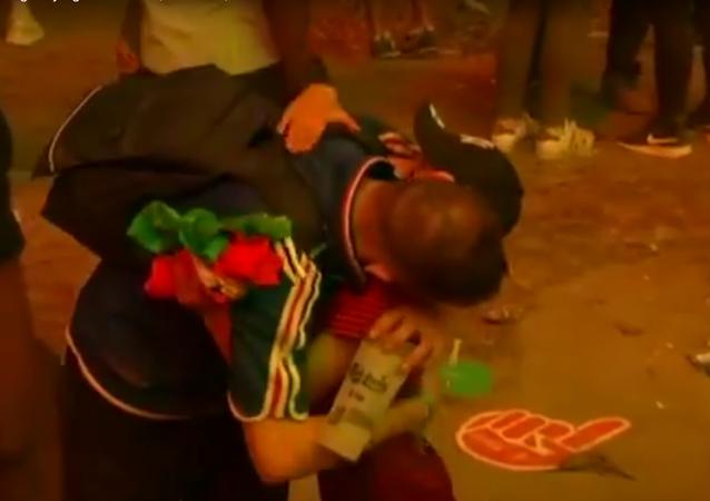 Malý portugalský fanoušek utěšuje francouzského fanouška po finále Eura 2016