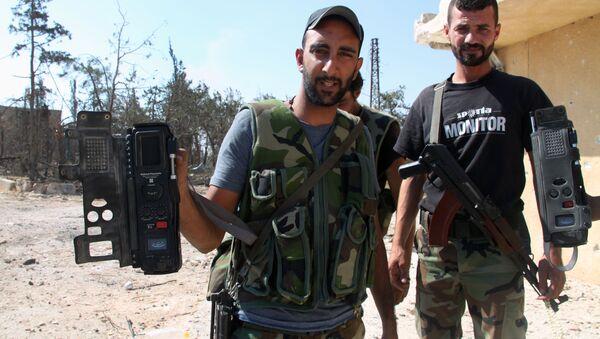 Syrští vojáci ukazují komunikační prostředky, které našli po teroristech - Sputnik Česká republika
