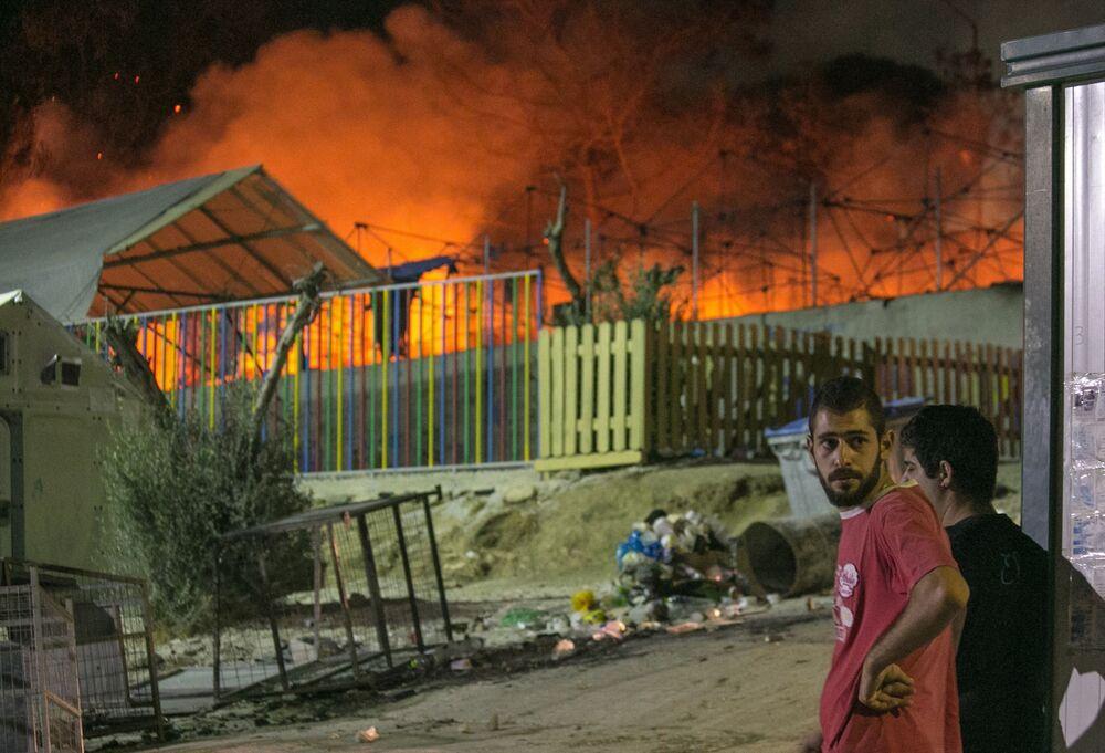 Migranti se dívají na požár v běženeckém táboru na severu řeckého ostrovu Lesbos