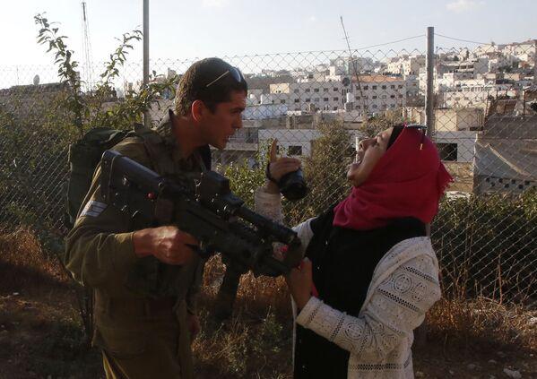Voják izraelské armády se pře s Palestinkou, která se pokouší natočit útok na vojáky v Hebronu - Sputnik Česká republika