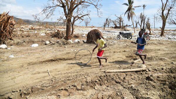 Děti ženou kolo v Les Cayes na Haiti, kam udeřil hurikán Matthew. Ilustrační foto - Sputnik Česká republika