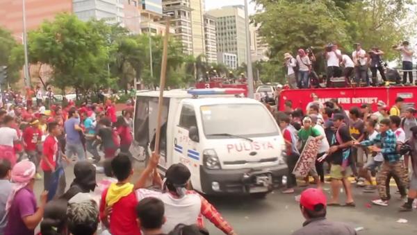 Policejní vozidlo najíždělo do protestujících u Velvyslanectví USA na Filipínách. VIDEO - Sputnik Česká republika