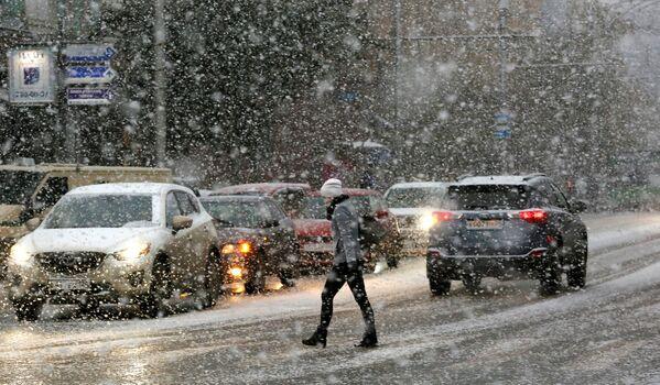 Žena přechází ulici za vánice v Krasnojarsku - Sputnik Česká republika
