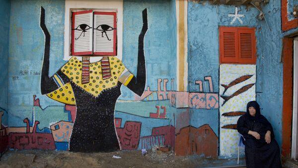 Žena s freskou egyptského malíře Alé Abula Hamada v pozadí v městě Burullus. Ilustrační foto - Sputnik Česká republika