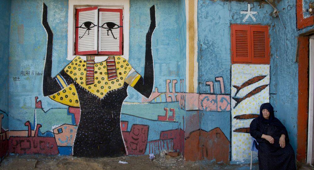 Žena s freskou egyptského malíře Alé Abula Hamada v pozadí v městě Burullus. Ilustrační foto