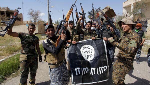 Iráčtí vojáci drží trofejnou vlajku Islamského státu - Sputnik Česká republika