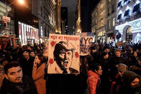 Účastníci protestní akce proti vítězství republikánského kandidáta Donalda Trumpa v prezidentských volbách před mrakodrapem Trump Tower v New Yorku - Sputnik Česká republika