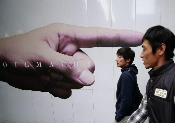 Muži u reklamních plakátů na ohradě staveniště v Tokiu, Japonsko - Sputnik Česká republika