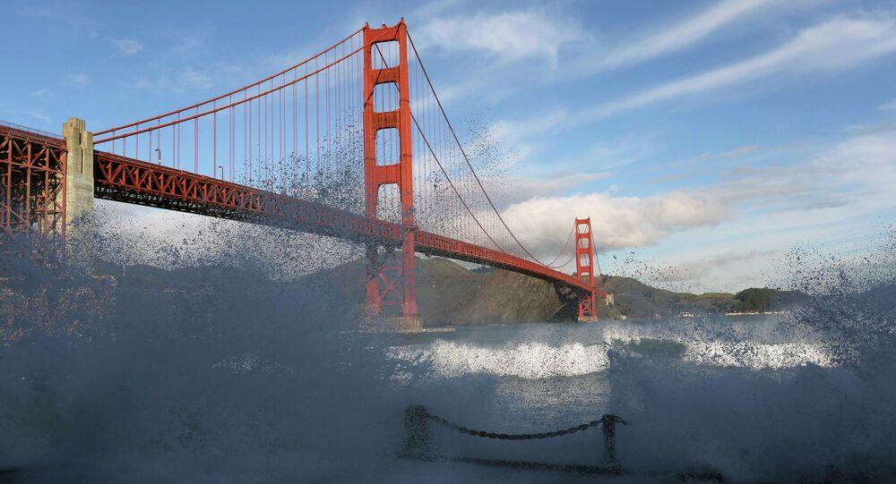 Waves crash against a sea wall in San Francisco Bay beneath the Golden Gate Bridge in San Francisco