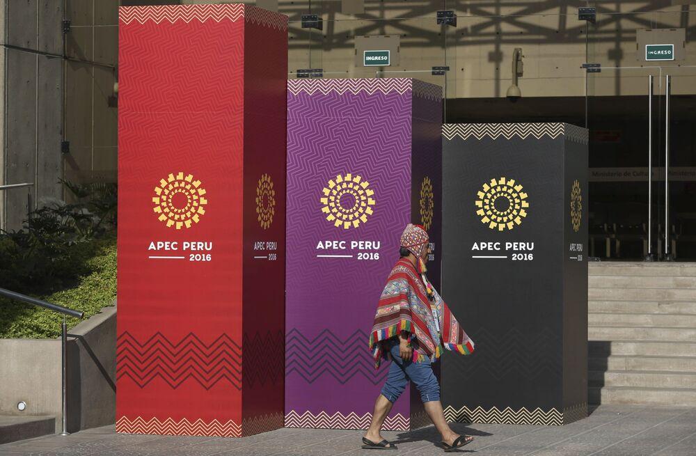 Muž v tradičním kroji jde kolem oficiáního loga mezinárodního summitu APEC