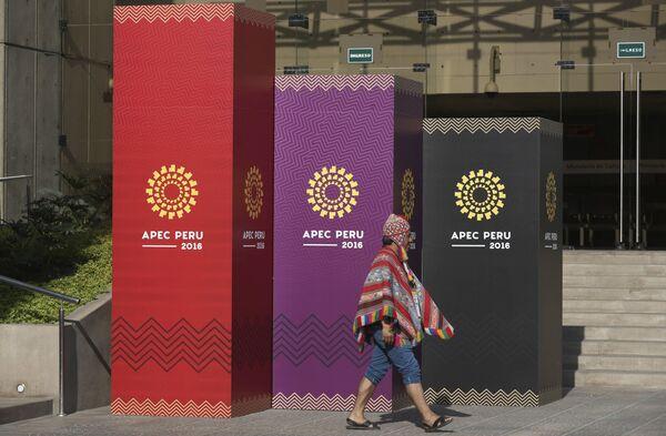Muž v tradičním kroji jde kolem oficiáního loga mezinárodního summitu APEC - Sputnik Česká republika