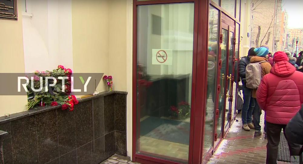 Lidé nesou květiny k budově souboru Alexandrovců v Moskvě