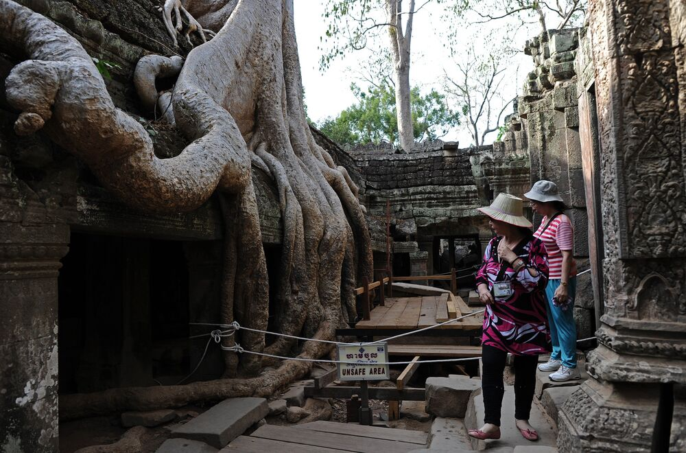 This picture taken on April 2, 2014 shows tourists visiting the Ta Phrom temple, part of the Angkor architectural complex in north-western Cambodia